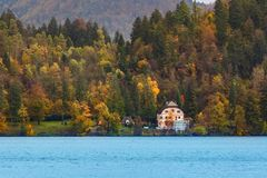 House by lake, autumn forest and mountains. With colorful fall trees stock photo