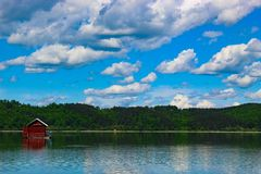 A house on the lake. A house on a lake with a background of forest. On a day and after a while, a heavy rain came on stock photo