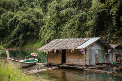 The house on the lake in the jungle. Floating house on the lake in the jungle . With parked the boat to the dock royalty free stock photo