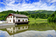 House on the lake. House reflected in lake Taria, Romania Royalty Free Stock Photos