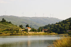 House at the lake with wind turbines Royalty Free Stock Image