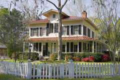 House with landscaped yard. Southern style home with beautiful garden and white picket fence Royalty Free Stock Photo