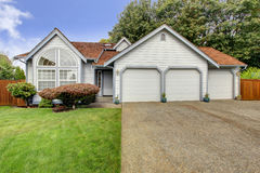 House with large arch window and three car garage. House exterior with orange tile roof, large arch window and three car garage Stock Image