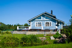 House on lawn. New blue wooden home on the lawn Stock Photo