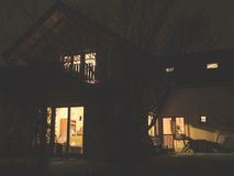 House of lights in evening. Shinning of light from the windows of house in the evening Stock Photography