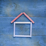House made of chalk on blue wooden background. Sweet home concep Royalty Free Stock Photo
