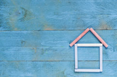 House made of chalk on blue wooden background. Sweet home concep Royalty Free Stock Image