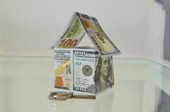 House made of 100 dollar bills and a key in front. House made of money and a key in front Royalty Free Stock Image