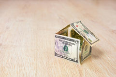 House made of dollar bills. Money house made of dollar bills on wooden background Royalty Free Stock Image