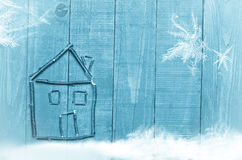 House made from dry sticks on wooden, blue background.Investments. Snow and snow flaks image. Stock Photography