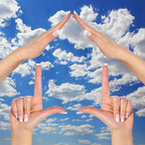 House made of female hands over blue sky with clouds. concept symbol home. House made of female hands over blue sky with clouds Royalty Free Stock Images