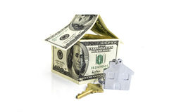 House made from hundred dollar bills and a key. Isolated against white background Royalty Free Stock Images
