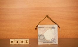 House made from the Indian currency notes and Home Loan in wooden block letters on wooden background.  royalty free stock photos