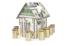 House made of money surrounded by a fence from coins Stock Images