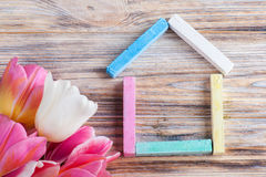 House made of multicolor chalks with tulips Royalty Free Stock Images