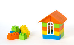 House made of plastic bricks and some blocks aside. Isolated on white background Stock Photo