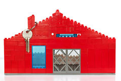 House made of plastic figurines. And metal key Royalty Free Stock Images
