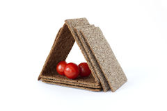 House made of rye crispbreads with Cherry tomatoes. House made from wholegrain rye crispbreads with Cherry tomatoes royalty free stock images