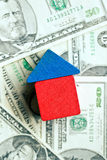 House made from wooden toy blocks on dollar background Stock Photos