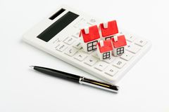 House maintenance cost calculation, mortgage and home loan or real estate price concept, group of miniature houses with red roof. On white clean calculator with royalty free stock image