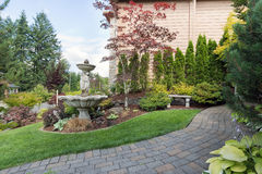 House Manicured Frontyard with Water Fountain. House manicured frontyard garden with water fountain stone bench green lawn plants trees shrubs and brick paver Stock Photography