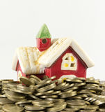 House and many coins on a white background Stock Photos