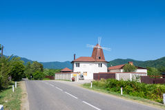 A house with a mill on a mountain road royalty free stock photo