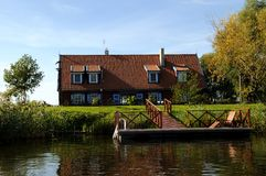 House on Minge riverside. House near Minge river with pier in the Minge village - Lithuanias small Venice Royalty Free Stock Photography