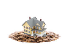 House miniature with pile of coins Stock Photo