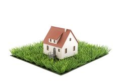 House miniature on square of green grass field. Isolated on white background stock photo
