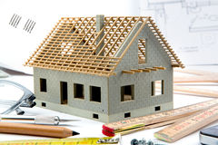 House miniature under construction on an architect desk Stock Photos