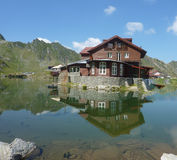 House mirroring in lake. Carpathian mountains in Romania Royalty Free Stock Images