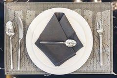 House modèle moderne italien : Plat blanc et serviette bleue avec l'ensemble de Dinning de cuillère d'argent et de fourchette Photo stock