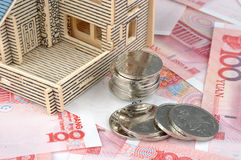 House model with banknote and coins. A house model with Chinese banknote and coins, means real estate, investment, expensive, and home building up Stock Photo