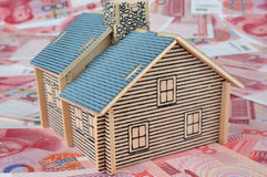 House model and bills. A house model with lot of Chinese currency RenMinBi, means real estate, investment, future, loan, credit, expensive, and home building up Royalty Free Stock Image