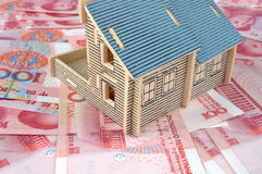 House model and bills. House model and lot of money, chinese currency, means payment, real estate market and expensive concept Stock Photography