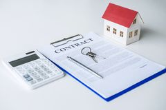 House model, calculator and house key lying on real estate contract, home loan and investment concept.  royalty free stock photography