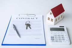 House model, calculator and house key lying on real estate contract, home loan and investment concept.  stock images