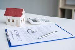 House model, calculator and house key lying on real estate contract, home loan and investment concept.  royalty free stock photo