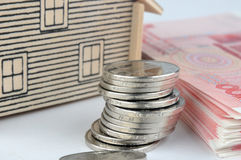 House model, coin and bills. House model and lot of money, chinese currency, including bills and coins, means payment, real estate market and expensive concept Stock Photos