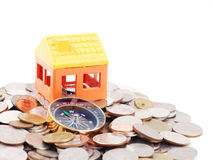 House model and compass. On coins background Stock Photos