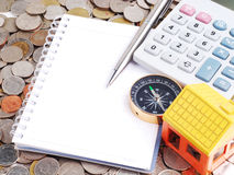 House model and compass with notebook on coins background. House model and compass and notebook on coins background Royalty Free Stock Image
