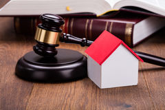 House Model With Gavel On Wooden Table. Close-up Of House Model With Gavel On Wooden Table In Courtroom Stock Photo