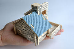 House model holding by hand. A house model is holding in the palm by an adult, means real estate and investment Stock Images
