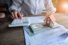 House model and money in hand, Concept of real estate and deal stock photo