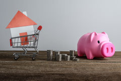 House model in shopping cart and row of coin money and piggy ban Stock Image