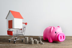 House model in shopping cart and row of coin money and piggy ban Royalty Free Stock Photography