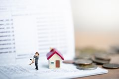 House model and small couple figures in love standing on bank passbook. royalty free stock image