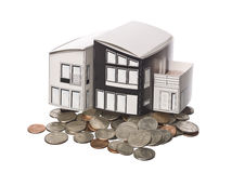 House model standing on american coins Royalty Free Stock Photos