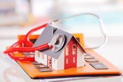 House modelo con el estetoscopio en el dispositivo de la calculadora fotos de archivo libres de regalías